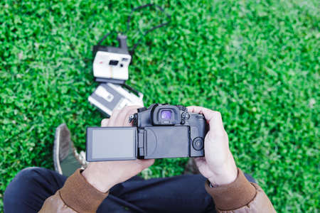 Upper view of a man taking a picture of two vintage cameras on the grass. Selective focus