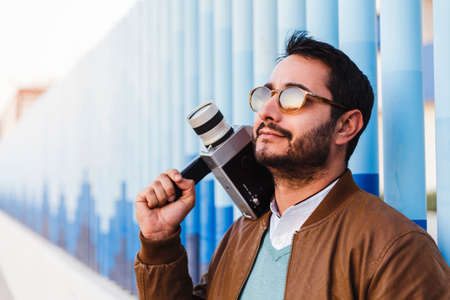 Bearded young standing with calm attitude holds a vintage super 8 camera. The model is wearing sunglasses and looks to the side of the frame. Vintage technology