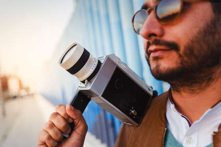 Bearded young man wearing sunglasses holds a vintage super 8 camera. Selective focus. Retro technology
