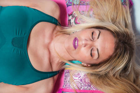 Close-up of a blonde woman lying on a savasana position. Eyes closed, serenity concept