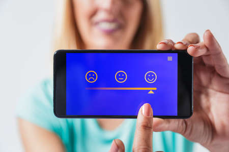 Blonde woman holding a smartphone. She is pointing to a happy face on a smartphone app. Selective focus, creative composition