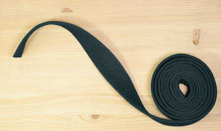grappling: Aikido black belt on  wooden background Stock Photo
