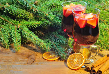 Two glasses of mulled wine, christmas tree branches and cinnamon sticks on wooden background Stock Photo