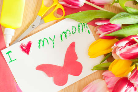 Bouquet of the tulips and card with greetings for mother