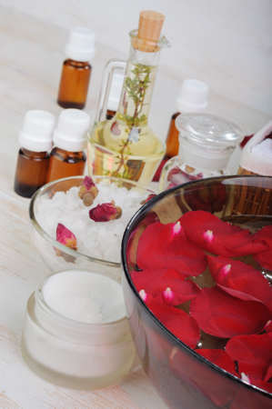 bath essence: Accessories for manicure: hand bath with rose petals, essentials oils,  bath salt, towels, cream. Close-up. Beauty and spa concept Stock Photo