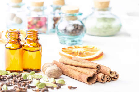 Essential oils in glass bottles maid from spices and nutmeg, cardamon, cinnamon, clove on wooden background 版權商用圖片