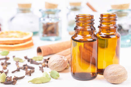 Essential oils in glass bottles maid from spices and nutmeg, cardamon, cinnamon, clove on wooden background Stock Photo