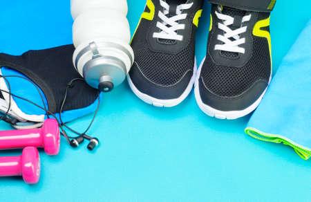 Pink dumbbells, sport bottle, headphones and black running shoes on the sport mat