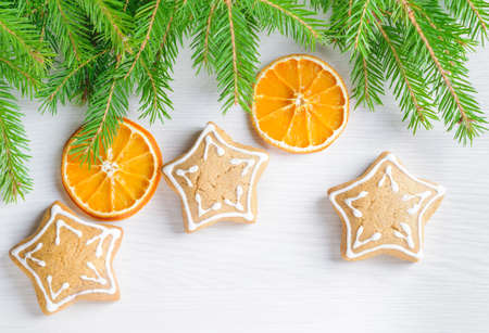 Gingerbreads and Christmas tree branches on the wooden background