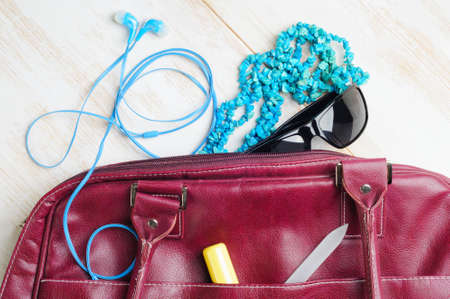 Woman's bag and it's content - lipstick, sunglasses, nail file, necklace, headphones