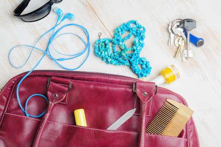 Woman's bag and it's content - lipstick, sunglasses, nail file, polish, necklace, headphones, keys, comb