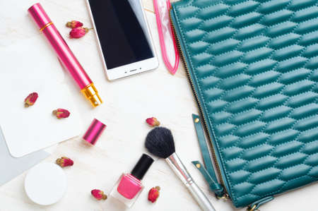 Woman's bag and it's content - nail file, polish, smartphone, wet napkins, perfume in travel applicator Imagens