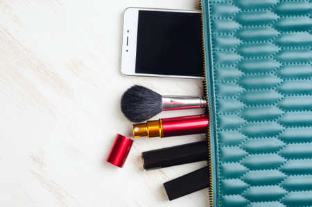 Woman's bag and it's content - lipstick, mascara, smartphone, perfume in travel applicator