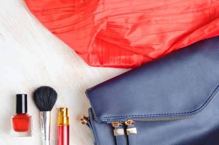 Woman's bag and it's content - nail polish, perfume in travel applicator, make-up brash, scarf Banco de Imagens