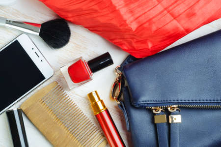 Woman's bag and it's content - nail polish, smartphone, mascara, perfume in travel applicator, comb, make-up brush, scarf Banco de Imagens