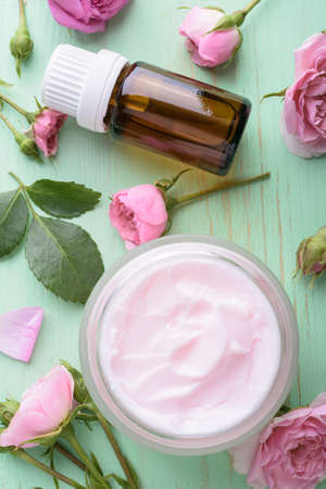 Homemade creame and essential oil with roses on wooden background Фото со стока