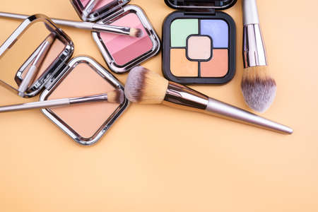 Flat view of cosmetics - lipstic, face-powder, brushes