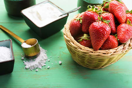 Strawberries in the basket on the wooden table Stock fotó