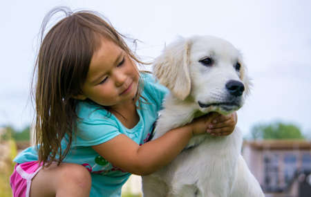 Baby girl hugging her Golden Retriever Puppy  Stock Photo - 14906358
