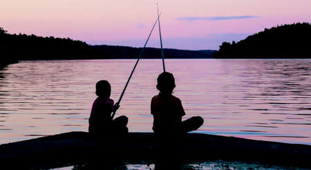 hombre pescando: Dos ni�os silueta pesca Foto de archivo