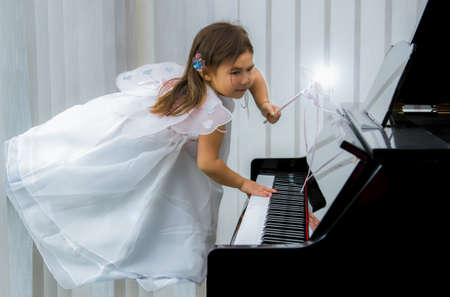 Child fairy levitating over piano and playing