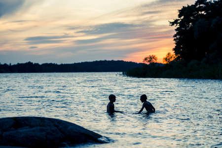 Best friends swimming after sunset Standard-Bild