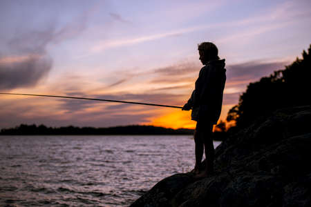 Young boy fishing in the sunset silhouette