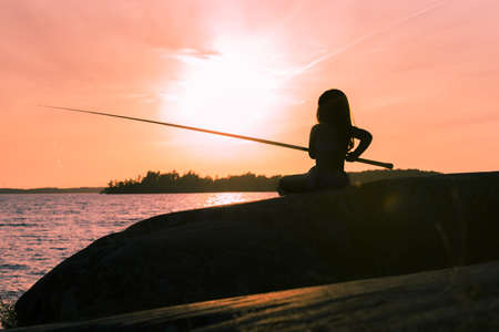 Young girl fishing in the sunset silhouette Standard-Bild
