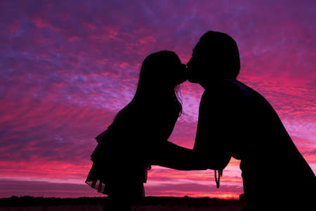Mother and daughter silhouette kiss in sunset Standard-Bild