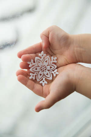 Snowflake on a childrens palm on a white background. Tenderness and trepidation
