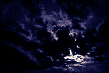 Dark night with thick clouds and the moon behind the clouds