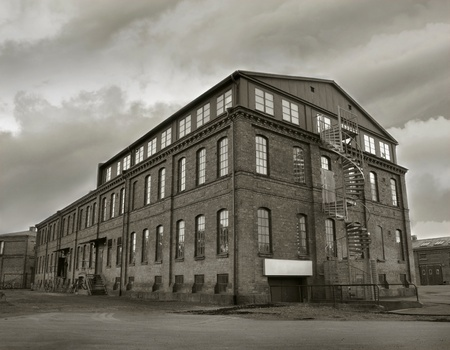 abandoned warehouse: Old depressing factory building in sepia tone. Symbol for economic depressions.