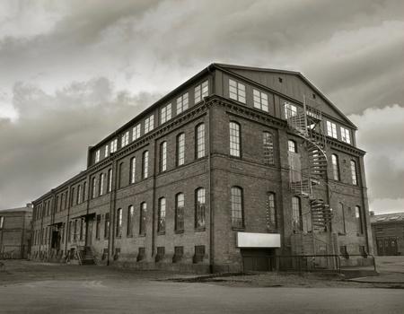 bedrijfshal: Oud deprimerend fabrieksgebouw in sepia toon. Symbool voor de economische depressies.
