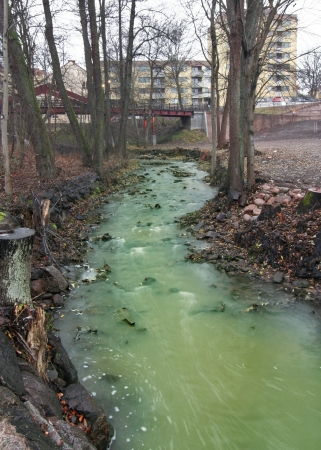 Green Polluted River in urban environment.
