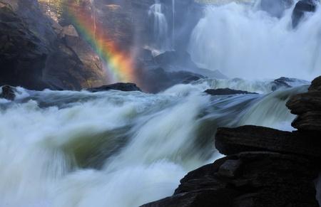 Raging river creates rainbow when steam meets sunlight.