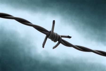 Barbed wire with dramatic background. Symbol for captivity and fear. photo