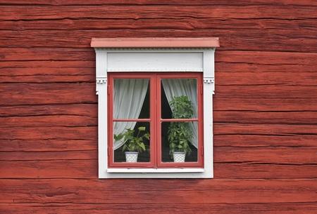 赤のスウェーデンの家の壁にかわいいウィンドウ