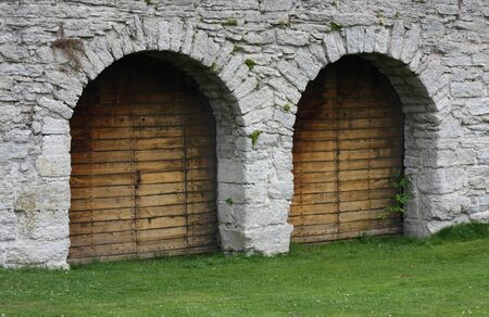 pick: Two wooden doorways in solid stone wall.