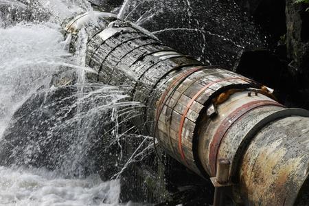 plomeria: Una tubería rota que las fugas de agua en todas direcciones. Foto de archivo