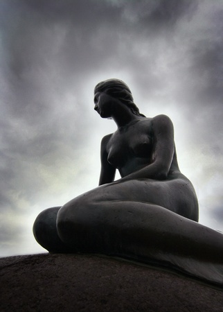 feministische: Bronzen beeld van zittende vrouw met dramatische achtergrond.