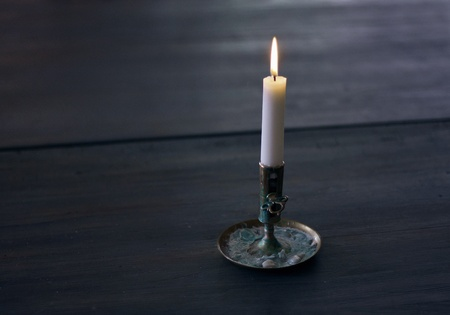 Lonely Candle on dark wooden table.