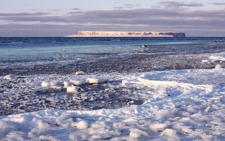 Frozen coastal landscape with island outside.