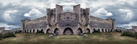Mighty medieval city wall defences in panorama with dramatic colors and sky