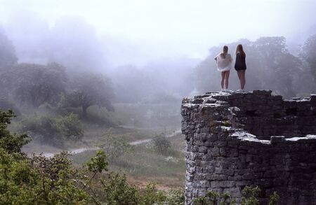 Young women overlooking beautiful, foggy valley from an ancient ruin
