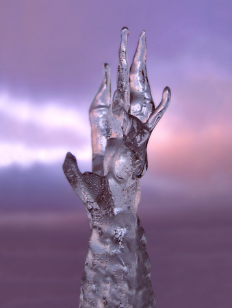 Hand of ice reaching for the dark sky. Symbol for giving the cold hand, frozen in time, natural ice sculptures and formations.