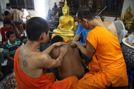 yantra: NAKHON CHAI, THAILAND - MAR 23: Buddhist monk makes traditional Yantra tattooing during Wai Kroo Master Day Ceremony in Wat Bang Pra on Mar 23, 2013 in Nakhon Chai, Thailand. Editorial