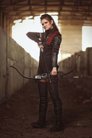 bowstring: Tribal girl in leather costume with tight bowstring inside abandoned building.