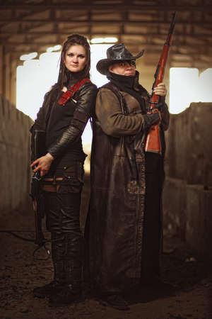 raider: Man with rifle in a leather garment and woman in raider costume with crossbow at post-apocalyptic world.