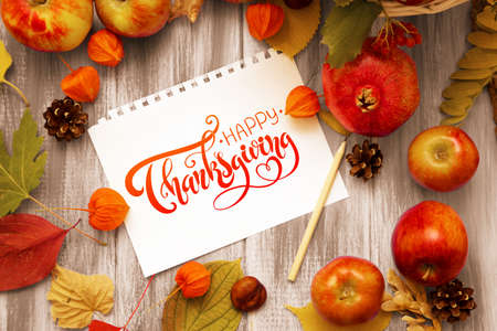 Thanksgiving - letters. Autumn bright background. Flowers, leaves and fruits on a blue wooden background. Background for the autumn holidays and thanksgiving day. Banque d'images