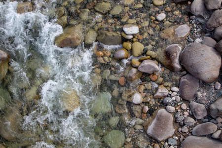 Water in the mountain raging river. Beautiful natural background of stones and water. Texture of clear water and fast river. Background to insert text.